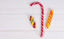 Вкусная тросточка конфеты и красочные яркие леденцы на палочке на деревянной доске Стоковые Фотографии RF
