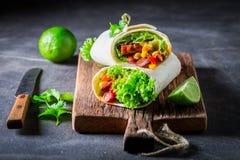Вкусное буррито с томатным соусом, овощами и мясом Стоковые Изображения