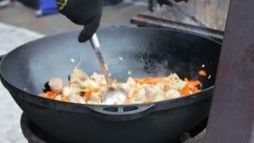 Вкусное, сочное мясо зажарено с овощами в огромном шаре и смешано с ложкой на фестивале еды улицы акции видеоматериалы
