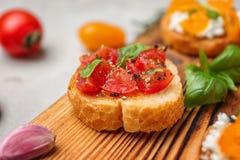 Вкусное bruschetta с томатами на деревянной доске, Стоковые Фото
