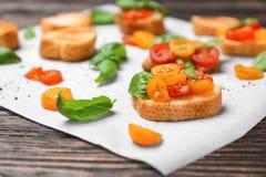 Вкусное bruschetta с томатами на пергаменте, Стоковые Изображения RF