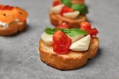 Вкусное bruschetta с томатами на серой предпосылке Стоковые Фотографии RF