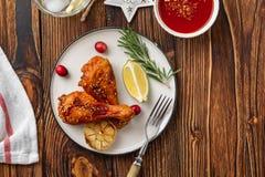 Вкусные аппетитные испеченные куриные ножки, который служат со специями, розмариновым маслом и клюквами на деревянной таблице пре стоковая фотография