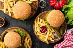 Вкусные бургеры, cheeseburgers, французские фраи, салат и красная ткань кухни шотландки Стоковая Фотография