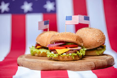 Вкусные гамбургеры с американскими флагами на деревянной доске Стоковые Изображения RF