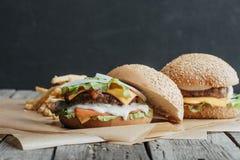 вкусные домодельные cheeseburgers на бумаге выпечки Стоковое Изображение