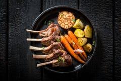 Вкусные зажаренные в духовке нервюры овечки с чесноком и овощами Стоковые Фото