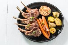 Вкусные зажаренные нервюры овечки с овощами на белой таблице Стоковое Изображение