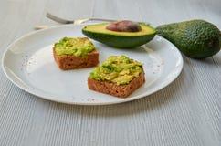 Вкусные здравицы авокадоа на белой плите с черными солью и чесноком Вегетарианские сандвичи авокадоа на серой предпосылке Стоковое Изображение RF