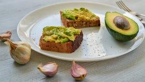 Вкусные здравицы авокадоа на белой плите с черными солью и чесноком Сандвичи авокадоа Vegan на серой предпосылке Стоковое Изображение RF