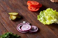 Вкусные ингридиенты гамбургера положены вне отдельно сверху, красиво гармонично, конец-вверх, взгляд сверху стоковое фото rf