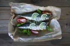 Вкусные испеченные все рыбы моря на бумаге выпечки Испеченный лещ моря с лимоном, травами, томатами, специями на предпосылке wood стоковое фото rf