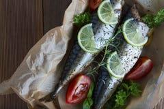 Вкусные испеченные все рыбы моря на бумаге выпечки Испеченный лещ моря с лимоном, травами, томатами, специями на предпосылке wood стоковые изображения