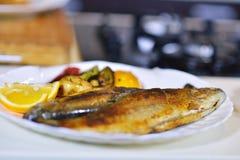 Вкусные испеченные рыбы на плите на конце-вверх таблицы Стоковые Фотографии RF