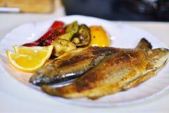 Вкусные испеченные рыбы на плите на конце-вверх таблицы Стоковое Фото