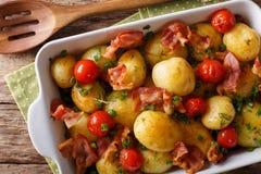 Вкусные новые картошки испекли с беконом, травами и макросом томатов внутри стоковые фото