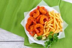 Вкусные обвалянные в сухарях зажаренные креветки и фраи француза Стоковая Фотография RF