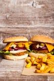 Вкусные домашние сделанные cheeseburgers на деревянной плите Стоковое Изображение