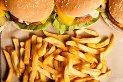 Вкусные домашние сделанные cheeseburgers на деревянной плите Стоковая Фотография