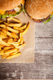 Вкусные домашние сделанные cheeseburgers на деревянной плите Стоковые Фотографии RF