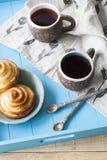 Вкусные плюшки с вареньем и 2 чашками чаю на голубом деревянном backgro Стоковые Изображения