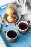 Вкусные плюшки с вареньем и 2 чашками чаю на голубом деревянном backgro Стоковая Фотография RF