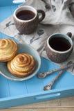 Вкусные плюшки с вареньем и 2 чашками чаю на голубом деревянном backgro Стоковое Фото