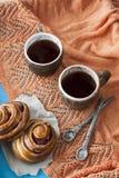 Вкусные плюшки с вареньем и 2 чашками чаю на голубом деревянном backgro Стоковое Изображение