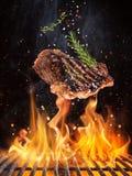 Вкусные стейки говядины летая над литым железом скрежещут с пламенами огня стоковое изображение