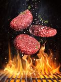 Вкусные стейки говядины летая над литым железом скрежещут с пламенами огня стоковое фото
