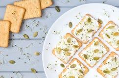 Вкусные шутихи с плавленым сыром, семенами и зелеными цветами Закуски на плите на серой таблице Здоровые закуски, взгляд сверху,  Стоковые Изображения