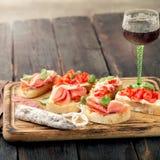 Вкусные bruschettas на разделочной доске с стеклом красного вина Стоковые Фото
