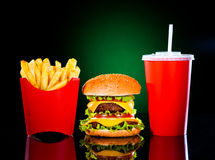 Вкусные fries гамбургера и франчуза на темноте - зеленом цвете Стоковые Изображения
