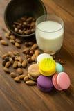 Вкусные macaroons и чашка молока с миндалиной на деревянной предпосылке Стоковое фото RF