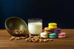 Вкусные macaroons и чашка молока с миндалиной на деревянной предпосылке Стоковое Изображение RF