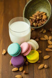 Вкусные macaroons и чашка молока с миндалиной на деревянной предпосылке Стоковые Изображения RF