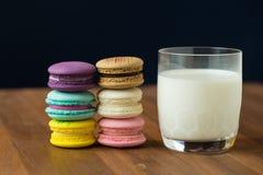 Вкусные macaroons и чашка молока с миндалиной на деревянной предпосылке Стоковые Фото