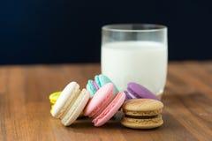 Вкусные macaroons и чашка молока с миндалиной на деревянной предпосылке Стоковые Фотографии RF