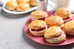 Вкусные scones с свернутыми сливк и вареньем на плите Стоковое Изображение