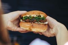 Вкусный бургер стильная женщина хипстера держа сочный гамбургер в руках закрывает вверх стоковые фото