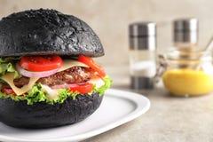 Вкусный бургер с черной плюшкой на таблице, Стоковые Фото