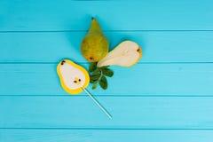 Вкусный леденец на палочке как груша на деревянной доске бирюзы около deliciou Стоковое фото RF