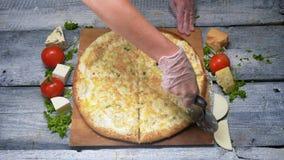 Вкусный отрезок пиццы с ножом ролика r Шеф-повар режет пиццу на деревянном подносе с профессиональным ножом перед сервировкой видеоматериал