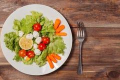 Вкусный салат с яичками томатов вишни, листьев салата, лимона, специй, моркови и триперсток на деревянном столе с вилкой Взгляд с Стоковое Изображение RF