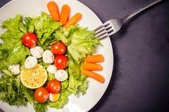 Вкусный салат с яичками томатов вишни, листьев салата, лимона, специй, моркови и триперсток на каменной таблице с вилкой Взгляд с Стоковое Изображение RF