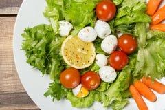 Вкусный салат с яичками томатов вишни, листьев салата, лимона, специй, моркови и триперсток на деревянном столе Взгляд сверху Стоковые Изображения
