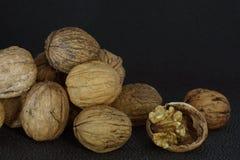 Вкусный стержень грецкого ореха на прерванной раковине около кучи грецких орехов Стоковые Фото