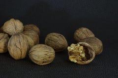 Вкусный стержень грецкого ореха на прерванной раковине среди других грецких орехов Стоковые Фото