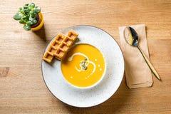 Вкусный суп сливк тыквы с кусками бельгийских waffles на белых плите и деревянном столе Кафе, ресторан или домашняя кухня Стоковые Изображения RF