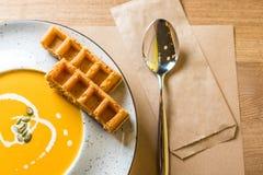 Вкусный суп сливк тыквы с кусками бельгийских waffles на белых плите и деревянном столе Кафе, ресторан или домашняя кухня Стоковое Изображение